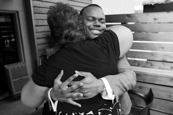 Goom hugs guest by Chicago Black & White Gay Wedding Photographer