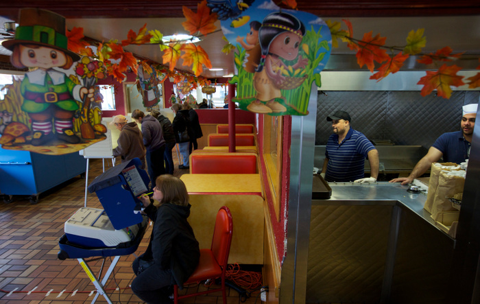Cooks Horacio Contrares and Juan Carvantes (R), look on as voters cast their ballots at Taquerias Los Comales on election day in Chicago, November 6, 2012. REUTERS/John Gress  (UNITED STATES)