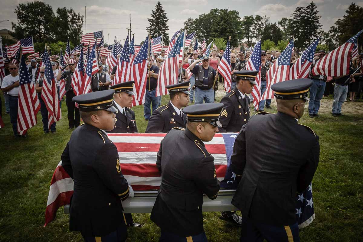 A United States Army honor guard carries the body of Sgt. Terry M. Lisk, who was killed in Iraq , to cemetery services in Lemont, Illinois, as the Partiot Guard Riders stand at attention in the background, July 8, 2006. by CHicago Photojurnalist John Gress