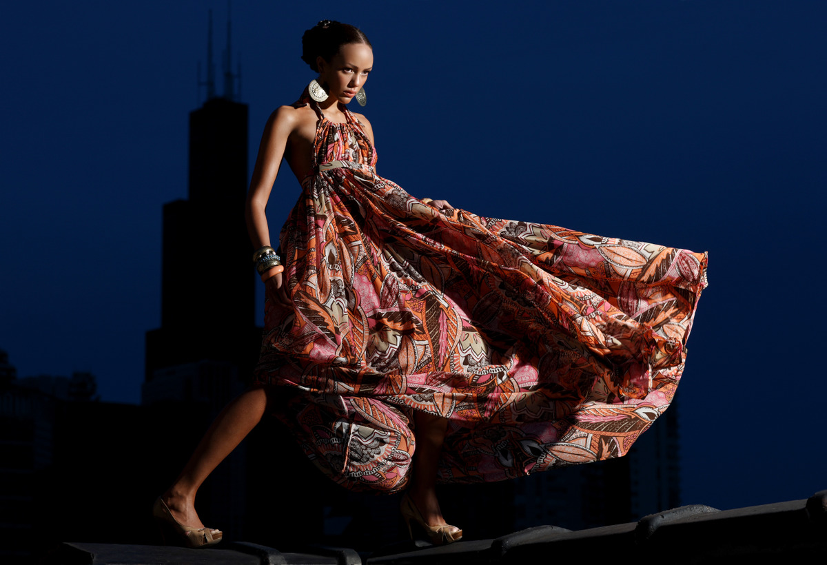A models poses on a Chicago rooftop in a red dress