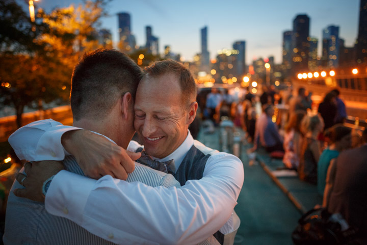 Gay grooms embrace at the end of their LGBT wedding in Chicago