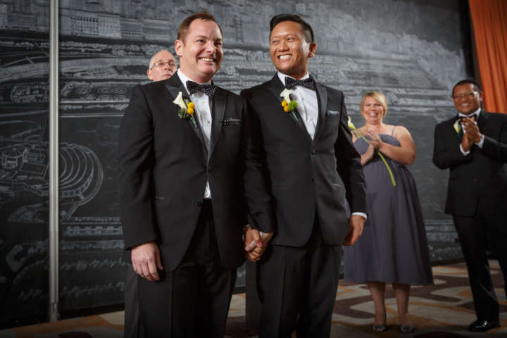 gay grooms smile after wedding in Chicago Illinois