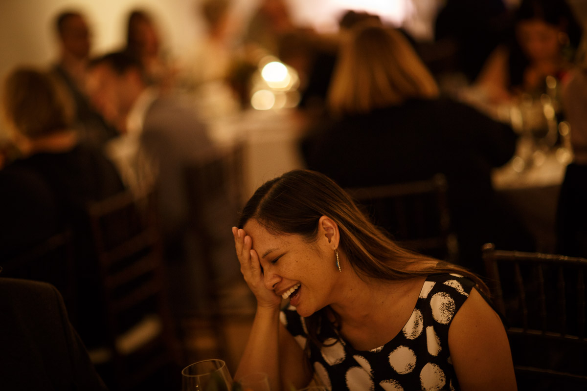 gay wedding guest laughs in Chicago same-sex wedding photography