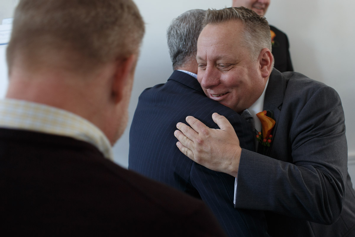 Illinois Gay Wedding Photographer captures groom hugging guest in Chicago