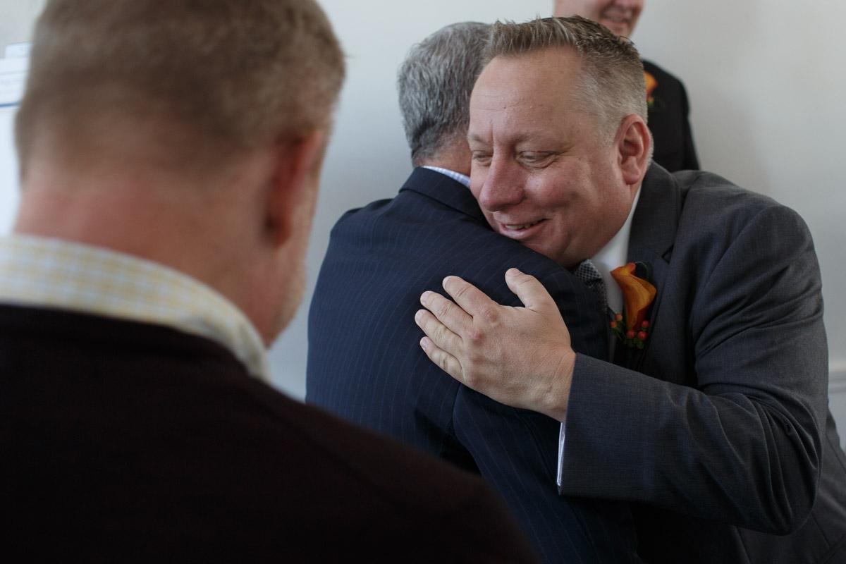 Illinois Gay Wedding Photographer captures groom hugging guest in Chicago