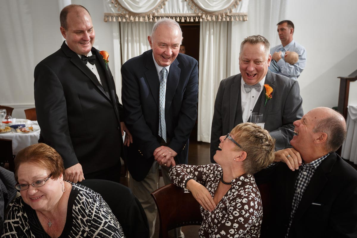 Family memebers laugh with gay grooms during their Chicago wedding