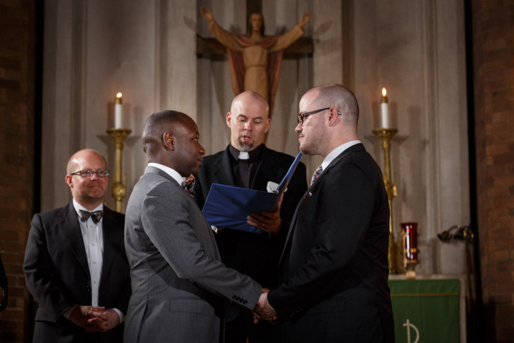 grooms at the alter during religious gay wedding in Chicago