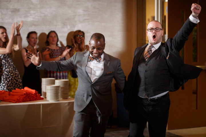 Chicago gay wedding photographer captures grooms triumphantly entering their recception