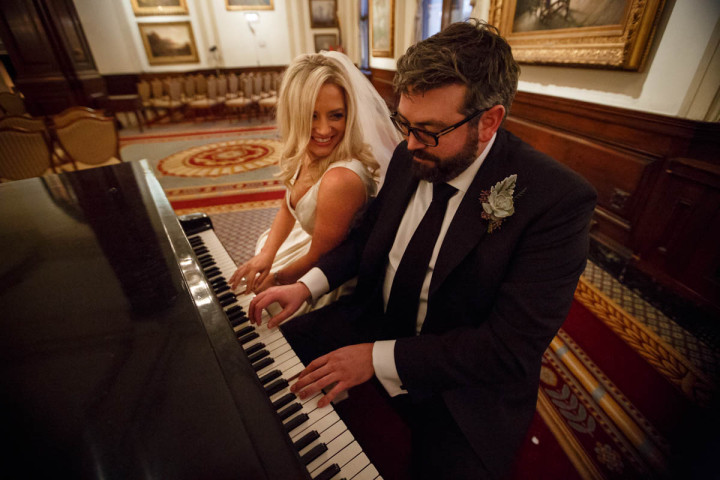 Chicago wedding photographer couple play the piano before their wedding ceremony