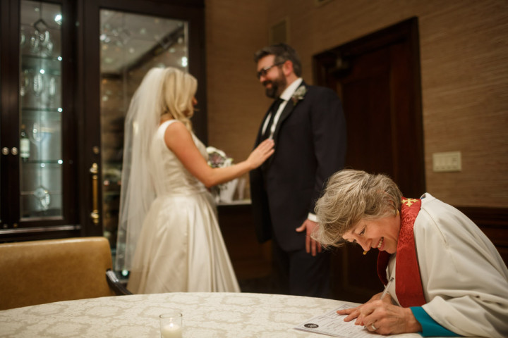 Chicago wedding photographer at union league club pastor signs marriage liscens