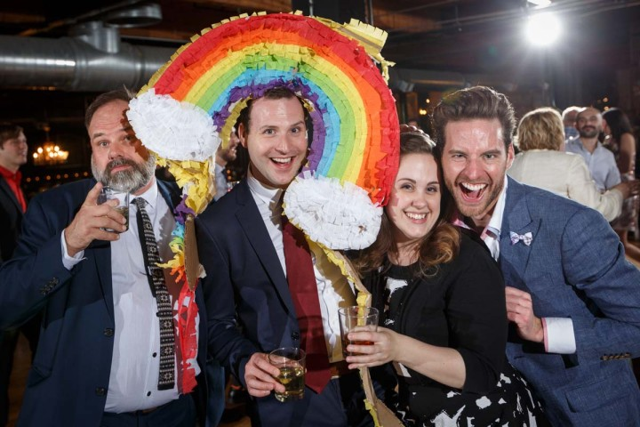Chicago Gay Wedding Photography of gay grooms with a rainbow pinata at Salvage One