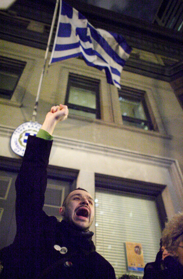 An Occupy Chicago protester shouts in front of the Greek flag as he demonstrates in solidarity with anti-austerity protesters in Greece, outside the Greek Consulate in Chicago February 16, 2012. REUTERS/John Gress