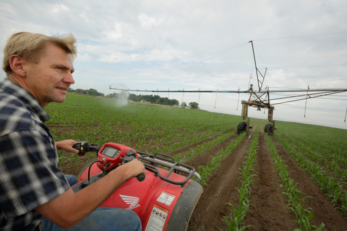 Farmer Dale Tuholski drives a four-wheeker through his cornfield next to a new pivot-irrigation system in Mill Creek, Indiana, June 11, 2012. When the weather doesnÕt cooperate, and the price of corn being what it is, you canÕt afford to go without rain,Ó said Tuholski, whose family installed seven new pivot-irrigation systems on their farm this year Ð and planHOLD FOR RELEASE-Farmer Dale Tuholski drives a four-wheeker through his cornfield next to a new pivot-irrigation system in Mill Creek, Indiana, June 11, 2012. When the weather doesnÕt cooperate, and the price of corn being what it is, you canÕt afford to go without rain,Ó said Tuholski, whose family installed seven new pivot-irrigation systems on their farm this year Ð and plan to purchase more. REUTERS/John Gress (UNITED STATES) to purchase more. REUTERS/John Gress