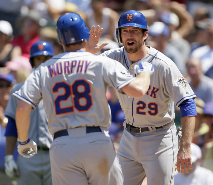 New York Mets Daniel Murphy is congratulated by teammate Ike Davis after he hit a two run home run off of the Chicago Cubs during the fourth inning in Chicago, June 27, 2012. REUTERS/John Gress