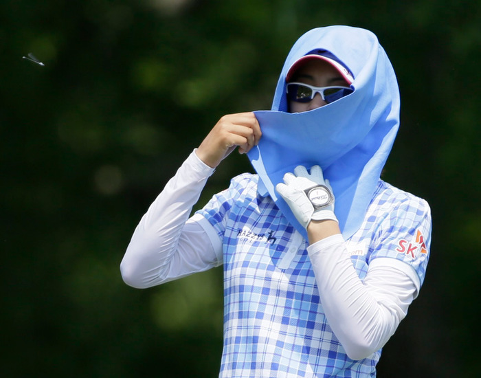 Choi Na-yeon of South Korea (R) wraps her head with a towel for protection against the sun and heat during the second round of the U.S. Women's Open golf tournament at Blackwolf Run in Kohler, Wisconsin July 6, 2012. REUTERS/John Gress
