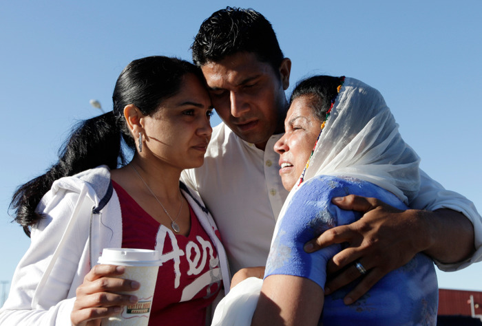 Mourners including Amardeep Kaleka (C), who's father Temple President Satwant Kaleka was killed, cry outside the scene of a mass shooting in Oak Creek, Wisconsin, August 6, 2012. A gunman killed six people and critically wounded three at a Sikh temple on Sunday before police shot him dead in an attack authorities are treating as an act of domestic terrorism. REUTERS/John Gress (UNITED STATES - Tags: CRIME LAW)