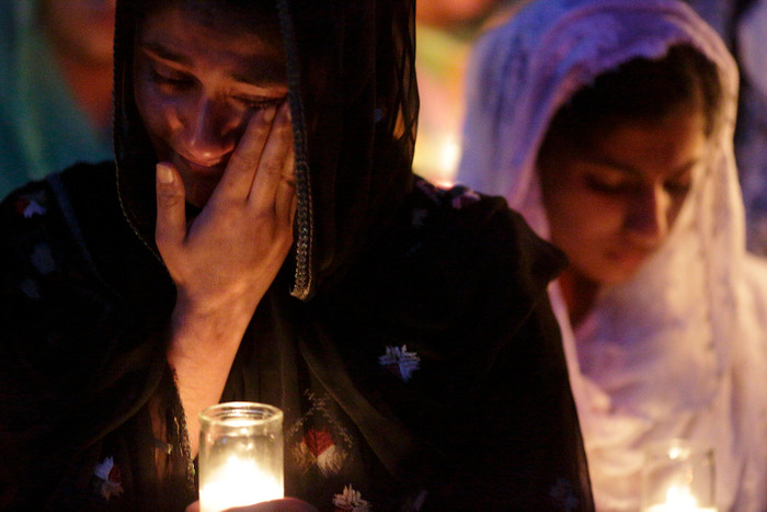 Mourners cry during a candlelight vigil at the Sikh Temple in Brookfield, Wisconsin, on August 6, 2012. A gunman killed six people and critically wounded three at a Sikh temple on Sunday before police shot him dead in an attack authorities are treating as an act of domestic terrorism. REUTERS/John Gress