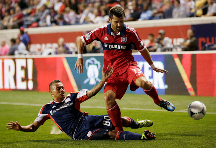 BRIDGEVIEW, IL - AUGUST 18:  Fernando Cardenas #80 of the New England Revolution slides into Gonzalo Segares #13 of the Chicago Fire in the first half during their MLS match at Toyota Park on August 18, 2012 in Bridgeview, Illinois. (Photo by John Gress/Getty Images)