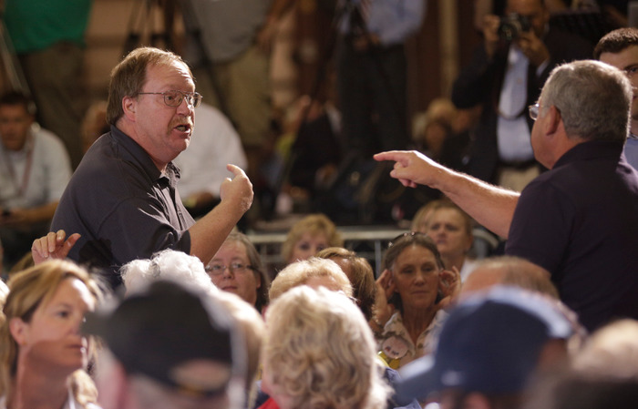 A man (L) who kept shouting at Republican U.S. presidential candidate Mitt Romney argues with another man in the audience as Romney campaigns at LeClaire Manufacturing in Bettendorf, Iowa, August 22, 2012. REUTERS/John Gress
