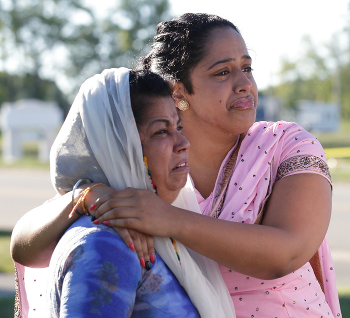 Mourners cry outside the scene of a mass shooting in Oak Creek, Wisconsin, August 6, 2012. A gunman killed six people and critically wounded three at a Sikh temple on Sunday before police shot him dead in an attack authorities are treating as an act of domestic terrorism. REUTERS/John Gress