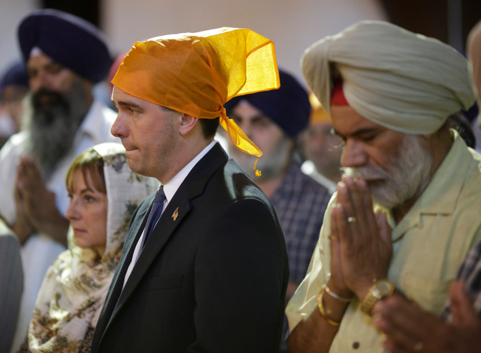 Wisconsin Governor Scott Walker attends a prayer service at the Sikh Temple in Brookfield, Wisconsin, on August 6, 2012. A gunman killed six people and critically wounded three at a Sikh temple on Sunday before police shot him dead in an attack authorities are treating as an act of domestic terrorism. REUTERS/John Gress