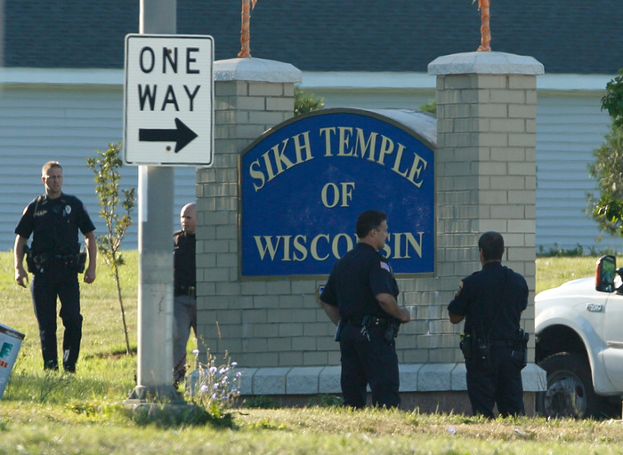Police stand outside the Sikh Temple of Wisconsin in Oak Creek, Wisconsin, August 6, 2012. A gunman killed six people and critically wounded three at a Sikh temple on Sunday before police shot him dead in an attack authorities are treating as an act of domestic terrorism. REUTERS/John Gress
