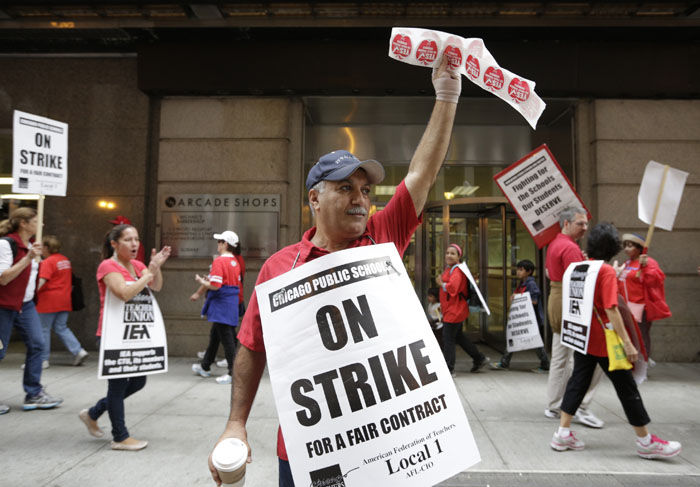 Chicago Teachers Union member and Math teacher Henry Pera pickets outside of the CPS headquarters in Chicago on the fourth day of their strike, September 13, 2012. REUTERS/John Gress