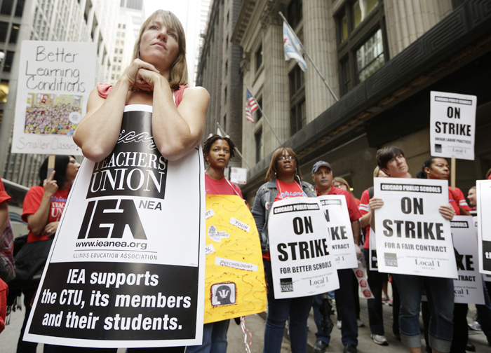 Chicago Teachers Union members, including Psycologist Jennifer Harte listen to an update about negotiations as they picket outside of the CPS headquarters in Chicago on the fourth day of their strike, September 13, 2012. REUTERS/John Gress