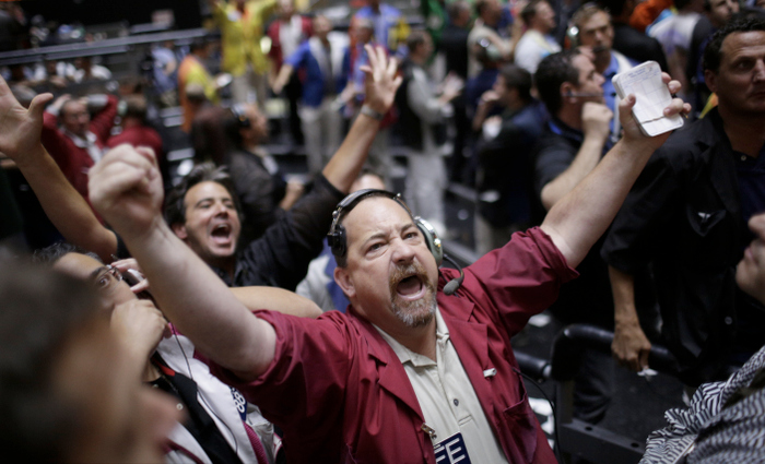 Trader Paul Duffy signals a trade in the S&P futures pit at the CME group in Chicago, September 13, 2012, after the Federal Reserve launched another aggressive stimulus program on Thursday, saying it will buy $40 billion of mortgage-related debt per month until the outlook for jobs improves substantially as long as inflation. REUTERS/John Gress (UNITED STATES)