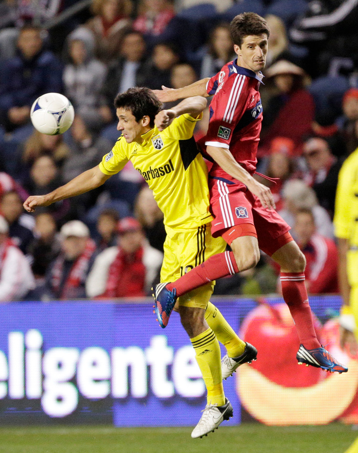 Bridgeview, IL - September 22:  Milovan Mirosevic #10 of the Columbus Crew and Alvaro Fernandez #4 of the Chicago Fire go up for the ball during the first half of their MLS soccer match at Toyota Park on September 22, 2012 in Bridgeview, Illinois. (Photo by John Gress/Getty Images)