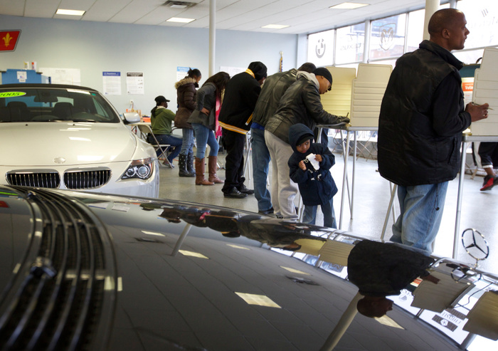 Voters cast their ballots next to cars during the U.S. presidential election at Sam's Auto Sales in Chicago, November 6, 2012. REUTERS/John Gress  (UNITED STATES)