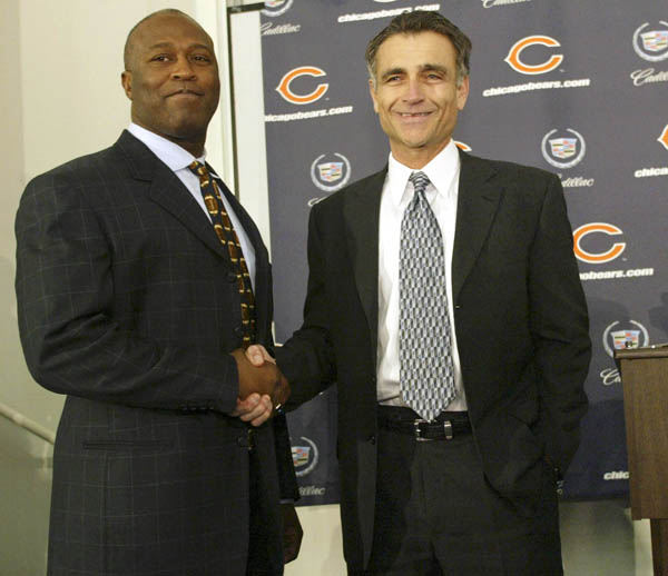 Lovie Smith, left, shakes hands with Chicago Bears General Manager Jerry Angelo as Smith is named the new head coach of the team in Lake Forest, Illinois Thursday, Jan 15, 2004. Smith was the St Louis Rams defensive coordinator. After turning around the Rams' defense, Smith will take on the Chicago Bears, which have only had one willing season in the past eight years. REUTERS/John Gress
