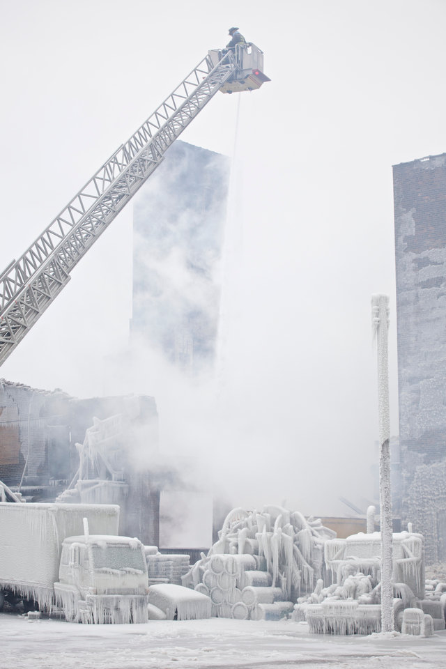 Firefighters spray hotspots on January 23, 2013 on an Ice covered warehouse that caught fire Tuesday night in Chicago. Fire Department officials said it is the biggest fire the department has had to battle in years. One-third of all Chicago firefighters were on the scene at one point or another trying to put out the flames. ÊAn Arctic blast continues to gripped theÊU.S. MidwestÊand Northeast Wednesday, with at least three deaths linked to the frigidÊweather, and fierce winds made some locations feel asÊcoldÊas 50 degrees below zero Fahrenheit. (minus 46 degrees Celsius) REUTERS/John Gress (UNITED STATES)