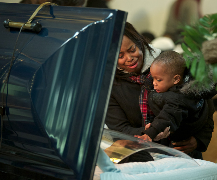 Jenyra Pendleton cries as she and her nephew Carlos Chambers view the body of Carlos' father Ronnie Chambers during funeral services on February 4, 2013 in Chicago. Shirley Chambers of Chicago had four children - three boys and a girl. Now they're all gone. Her son, Ronnie Chambers. was the last of the single mother's children - all victims of gun violence in Chicago over a period of 18 years. REUTERS/John Gress