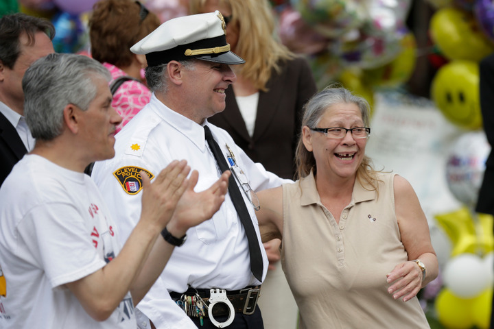 Nancy Ruiz, mother of Gina DeJesus, hugs a police officer as her daughter arrives at her home in Cleveland, Ohio, May 8, 2013. DeJesus, Michelle Knight, Amanda Berry and Berry's 6-year-old daughter escaped a Cleveland home where they were held captive. DeJesus, now 23, vanished aged 14 in 2004. REUTERS/John Gress (UNITED STATES - Tags: CRIME LAW)