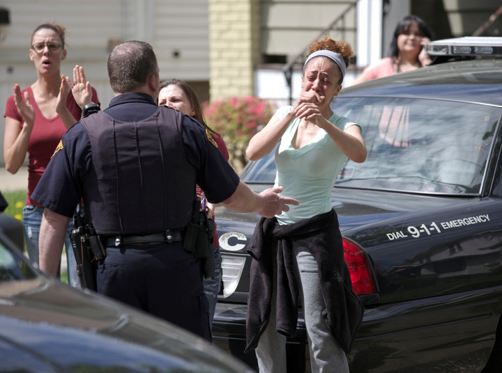 Neighbors react as Amanda Berry arrives at her sister's home in Cleveland, Ohio, May 8, 2013. Berry, Gina DeJesus, Michelle Knight and Berry's 6-year-old daughter escaped a Cleveland home where they were held captive. Berry, now 27, was found with her daughter, conceived and born during her captivity, along with DeJesus, 23, who vanished aged 14 in 2004, and Knight, 32, who was 20 when she went missing in 2002. REUTERS/John Gress (UNITED STATES - Tags: CRIME LAW TPX IMAGES OF THE DAY)