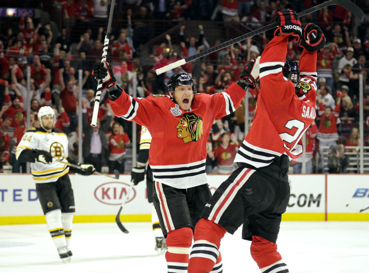 Chicago Blackhawks right wing Marian Hossa (C) celebrates teammate Brandon Saad's (R) second period goal as Boston Bruins defenseman Dennis Seidenberg (44) looks on during Game 1 of their NHL Stanley Cup Finals hockey series in Chicago, Illinois, June 12, 2013. REUTERS/John Gress