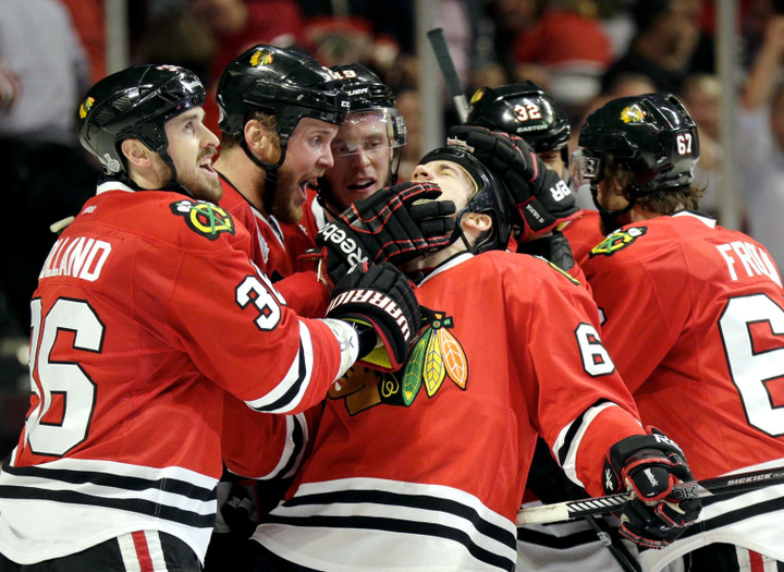Chicago Blackhawks center Andrew Shaw (C) celebrates his game-winning triple overtime goal against the Boston Bruins with teammates Dave Bolland (36), Brandon Saad (20) and Jonathan Toews (19) during Game 1 of their NHL Stanley Cup Finals hockey series in Chicago, Illinois, June 13, 2013. REUTERS/John Gress