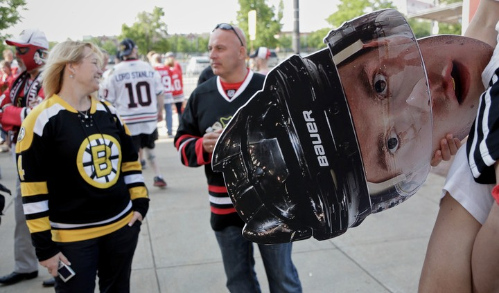 Chicago Blackhawks fans Sebastian Smith (R) holds a cutout of the head of Chicago Blackhawks' Jonathan Toews as he rides on the shoulders of his father Chris before Game 2 of their NHL Stanley Cup Finals hockey series in Chicago, Illinois, June 15, 2013. REUTERS/John Gress (UNITED STATES - Tags: SPORT ICE HOCKEY)