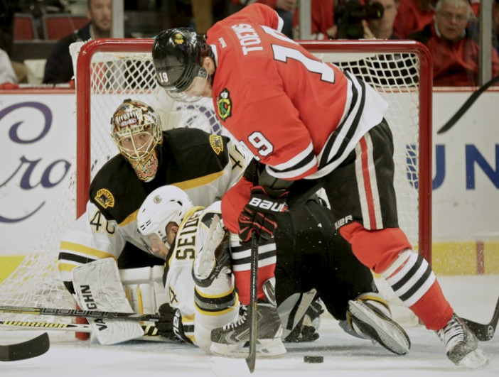 Boston Bruins goalie Tuukka Rask (L) keeps his eyes on the puck as Dennis Seidenberg (C) defends Chicago Blackhawks Jonathan Toews during Game 2 of their NHL Stanley Cup Finals hockey series in Chicago, Illinois, June 15, 2013. REUTERS/John Gress (UNITED STATES - Tags: SPORT ICE HOCKEY)