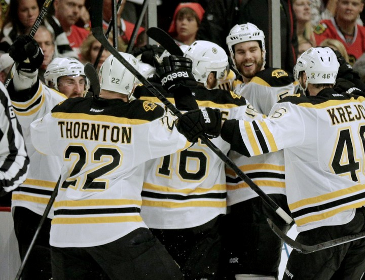 Boston Bruins left wing Daniel Paille (20) is mobbed by teammates after scoring in overtime against the Chicago Blackhawks during Game 2 of their NHL Stanley Cup Finals hockey series in Chicago, Illinois, June 15, 2013. REUTERS/John Gress (UNITED STATES - Tags: SPORT ICE HOCKEY)