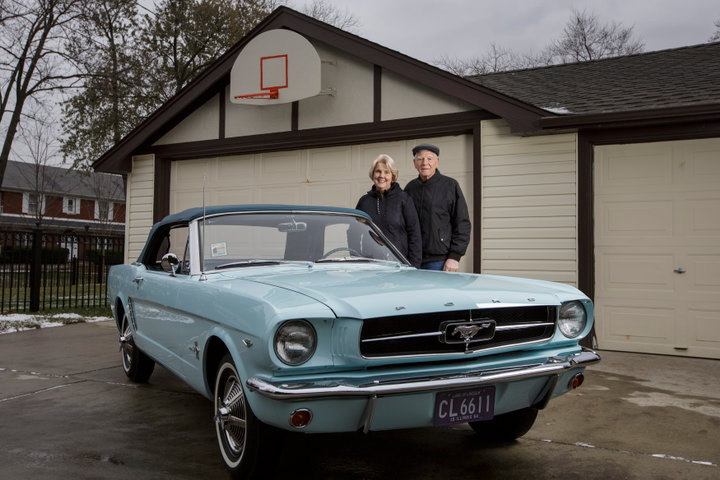 Tom (L) and Gail Wise pose with Gail's Skylight Blue 1964 1/2 Ford Mustang convertible outside their garage where it sat for 27 years before its restoration, in Park Ridge, Illinois November 26, 2013. Gail Wise, then using her maiden name of Gail Brown, made the first known retail purchase of a Mustang on April 15, 1964, two days before the model went on sale. Ford will unveil its next-generation 2015 Mustang on December 5, 2013 for the model's 50th anniversary with simultaneous events in Michigan, Shanghai, Sydney, Barcelona, New York and Los Angeles.