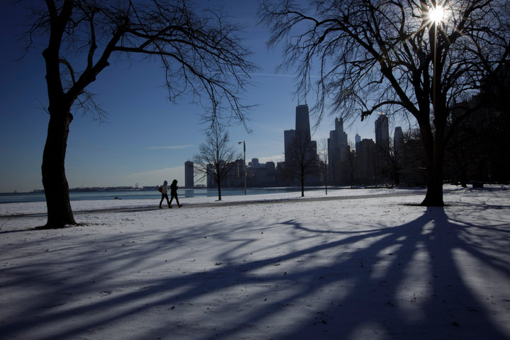 Two women walk along the shore of Lake Michigan In Chicago where temperatures have dropped well below freezing. REUTERS/John Gress (UNITED STATES)