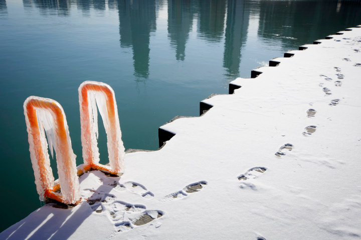Footprints can be seen along the ice covered shore as the reflection of the skyline can be seen on the surface of Lake Michigan In Chicago where temperatures have dropped well below freezing. REUTERS/John Gress (UNITED STATES)