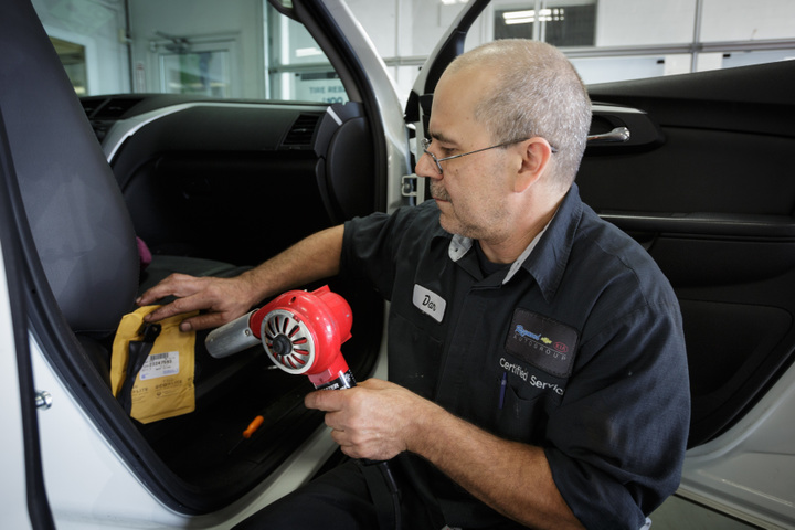 Technician Dan Lutka does a seat belt recall on a Chevy Traverse at Raymond Chevrolet in Antioch, Illinois, July 17, 2014. REUTERS/John Gress (UNITED STATES)