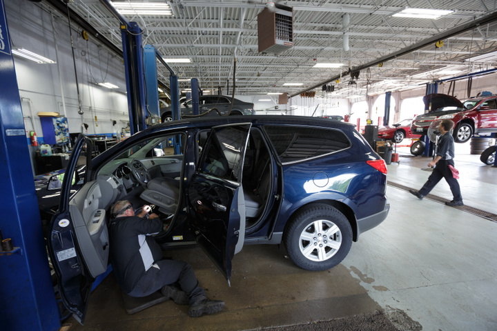 Technician Bob Poe works on a wiring recall under the drivers seat of a Chevy Traverse at Raymond Chevrolet in Antioch, Illinois, July 17, 2014. REUTERS/John Gress (UNITED STATES)