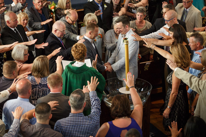 Wedding photography captures LGBT couple being blessed at a hurch in Chicago