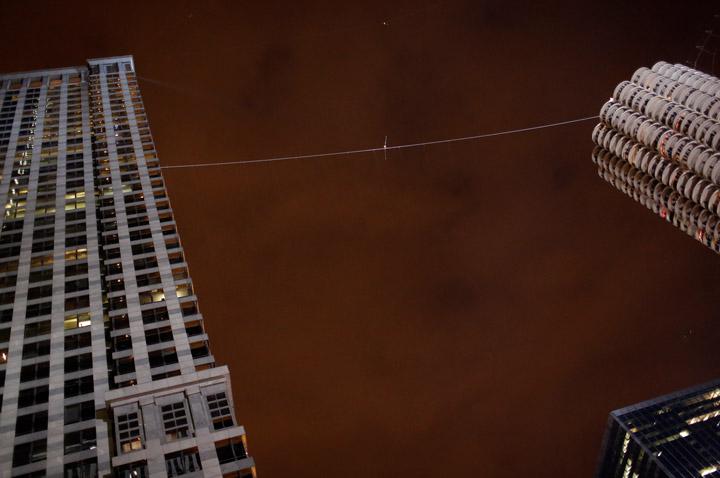 Daredevil Nik Wallenda walks a tightrope over the Chicago river.