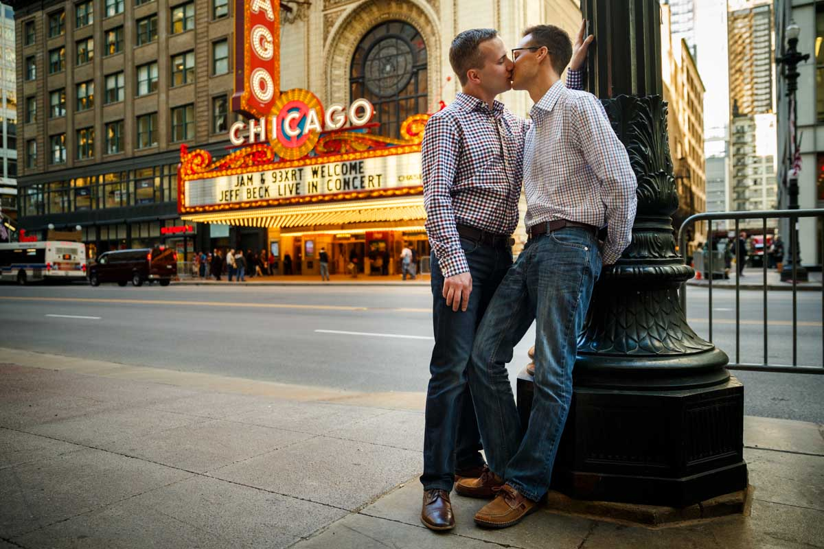 Illinois LGBT Wedding Photography engagement session with couple in front of the Chicago Theatre
