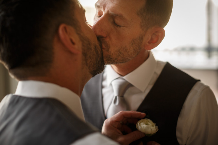 grooms kiss while getting dressed by Chicago gay wedding photojournalist